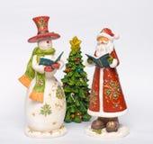 Snögubbe och jultomten som sjunger jullovsånger royaltyfri bild