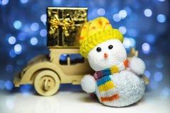 Snögubbe och träbil med gåvaasken Arkivfoton