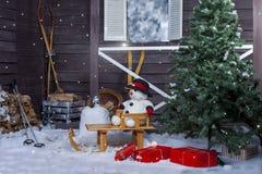 Snögubbe på en träsläde Arkivfoto