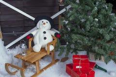 Snögubbe på en träsläde Royaltyfri Foto