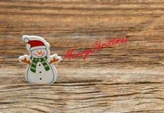 Snögubbe på träbakgrund Royaltyfri Foto