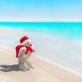 Snögubbear kopplar ihop på havsstranden i julhatt Arkivfoto