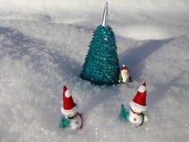 Snögubbear nära den konstgjorda julgranen i snön Arkivfoto