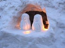 Snögubbedockavänner i en isgrotta med stearinljuset tänder royaltyfria bilder