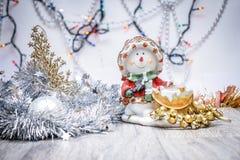 Snögubbeljusstakenärbild med den festliga girlanden Mot bakgrunden av kulöra ljus royaltyfria bilder