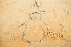 Snögubben av vaggar i sand på stranden Arkivfoton