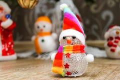 Snögubben i ett lock och en randig halsduk kostar på ett golv nära ettträd mot bakgrunden av annan snögubbear och fader Frost fotografering för bildbyråer