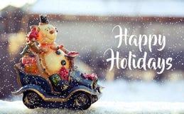 Snögubben rider en bil med gåvor, lycklig feriebakgrund royaltyfri fotografi