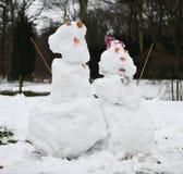 Snögubbepar i vintrig trädgård Royaltyfri Bild