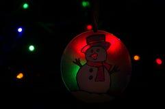 Snögubbeprydnad i glödande ljus Royaltyfria Bilder