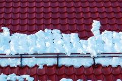 Snöhållare och Red Roof tegelplattor på huset arkivfoton