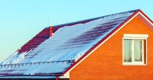Snöhållare och Red Roof tegelplattor på huset royaltyfria bilder