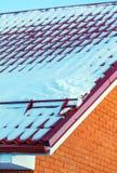 Snöhållare och Red Roof tegelplattor på huset royaltyfri foto