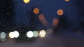 Snöig afton på staden Vatten tappar på det glass fönstret för vindrutan, billjus ut ur fokusbakgrund stock video