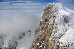 Snöig alpin bergssida med moln Royaltyfria Bilder