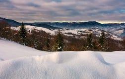 Snöig backar i bergig bygd arkivfoto
