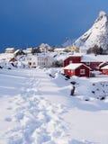 Snöig bana i by av A på Lofoten, Norge Arkivfoto