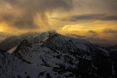 Snöig berg för vinter Bergssida som täckas av snö Molnig aftonhimmel royaltyfria bilder