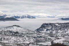 Snöig berg med dimma Arkivbild