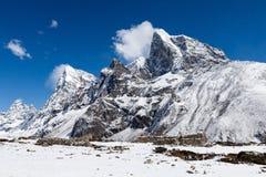 Snöig berg nära den Dingboche byn på vägen royaltyfri bild