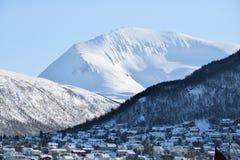 Snöig berg på en ljus solig dag med längst ner hus Royaltyfri Fotografi