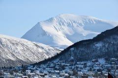 Snöig berg på en ljus solig dag med längst ner hus Royaltyfri Foto