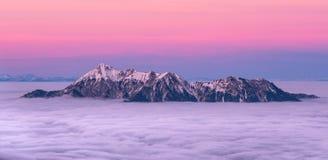 Snöig bergblast som täckas i moln med härlig rosa himmel arkivbild