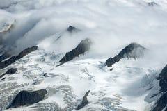 Snöig bergkanter i molnen, Kluane nationalpark, Yukon Royaltyfri Bild