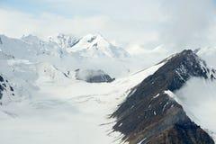 Snöig bergmaxima i molnen, Kluane nationalpark, Yukon Arkivbilder