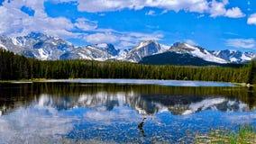 Snöig bergreflexioner i den lugna sjön royaltyfri fotografi