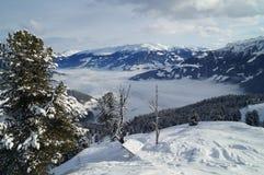 Snöig bergsikt av fjällängarna och en dal i molnen Arkivfoto