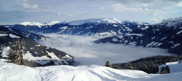 Snöig bergskedja med den dimmiga dalen Royaltyfria Bilder