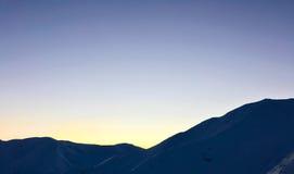 Snöig bergsolnedgång för vinter arkivfoto
