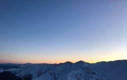 Snöig bergsolnedgång för vinter arkivbild