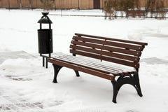 Snöig bruntträdgårdbänk i parkera Royaltyfri Foto