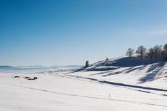 Snöig dal upptill av berget med en klar blå himmel på en solig dag med fallande snöflingor royaltyfria bilder
