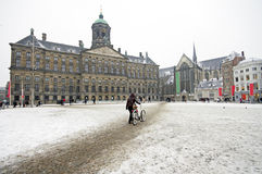 Snöig damsquare med Royal Palace i Amsterdam Arkivfoton