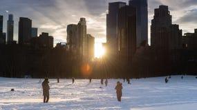 Snöig fält, folk och New York horisont på solnedgången Arkivbild