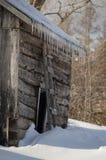 Snöig gammal ladugård för journalkabin med istappar Royaltyfria Bilder