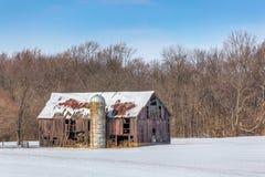 Snöig gammal ladugård och silo Royaltyfria Bilder