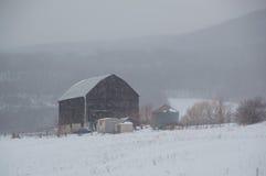 Snöig gammal svart ladugård i snöstorm med kullar Royaltyfri Bild