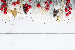 Snöig granträd och julpynt på den vita träbästa sikten för tabell Lekmanna- lägenhet arkivbilder