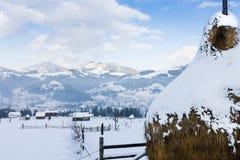 Snöig höstack på en bakgrund av en by i bergen Arkivfoto