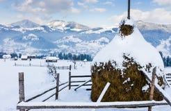 Snöig höstack på en bakgrund av en by i bergen Arkivfoton