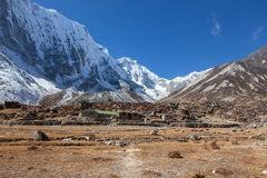Snöig Himalayan berg och Nepaliby in Royaltyfria Bilder