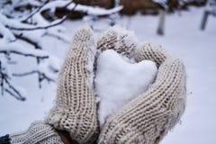 Snöig hjärta i trähandske Arkivfoto
