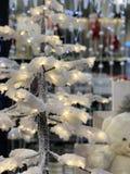 Snöig julgran och glödande girlander arkivbilder