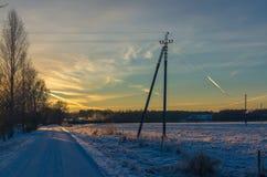 Snöig landsgränd vid ett fält och by på solnedgången arkivfoton