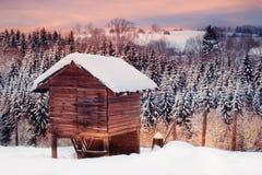 Snöig landskap för vinter med träkojan i skogen inom solnedgång royaltyfri bild