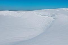 Snöig landskap med flodstranden i en solig winderdag Arkivbild